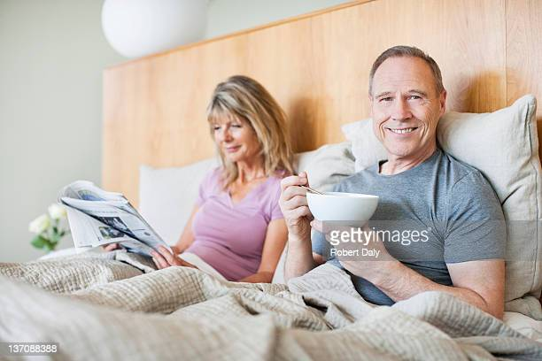 Senior couple eating cereal and reading newspaper in bed