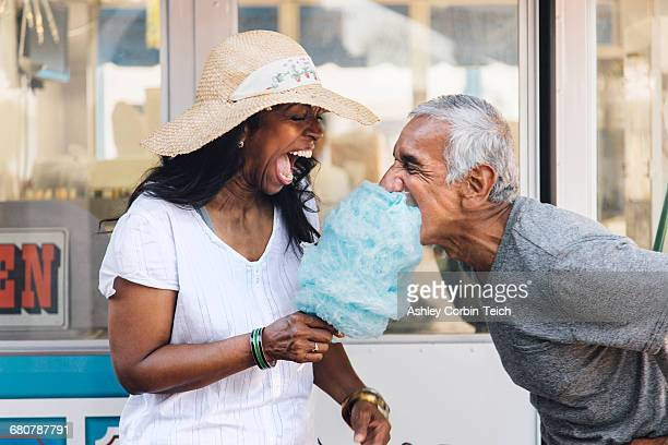 senior couple eating cotton candy, laughing, long beach, california, usa - 60 69 anos imagens e fotografias de stock