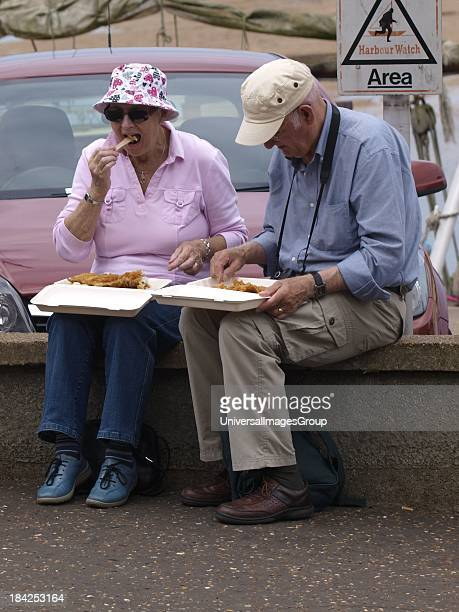 Senior couple eating fish and chips, Wells-Next-The-Sea, Norfolk. UK.