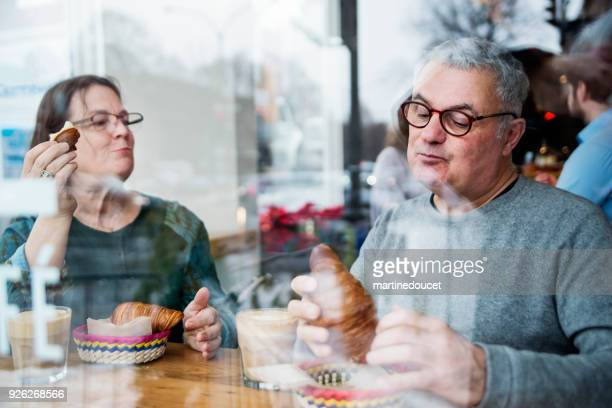 "senior couple eating in a small local bakery shop. - ""martine doucet"" or martinedoucet stock pictures, royalty-free photos & images"