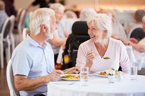 Senior Couple Eating Meal And Talking In Retirement Home 1047536906
