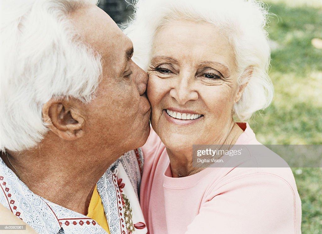 Senior Couple Embrace, Man Kissing the Woman's Cheek : Stock Photo