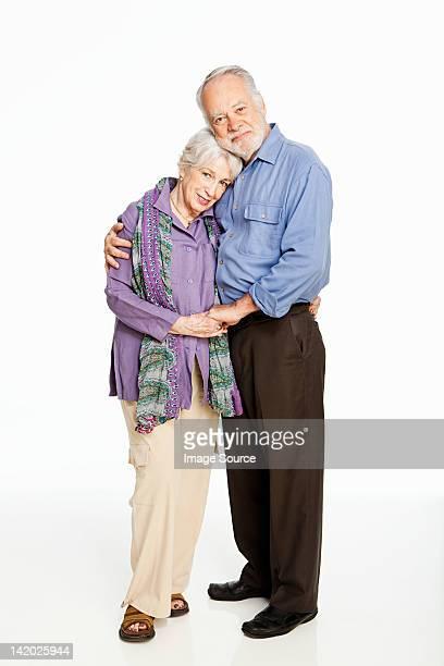 Senior couple embracing against white background