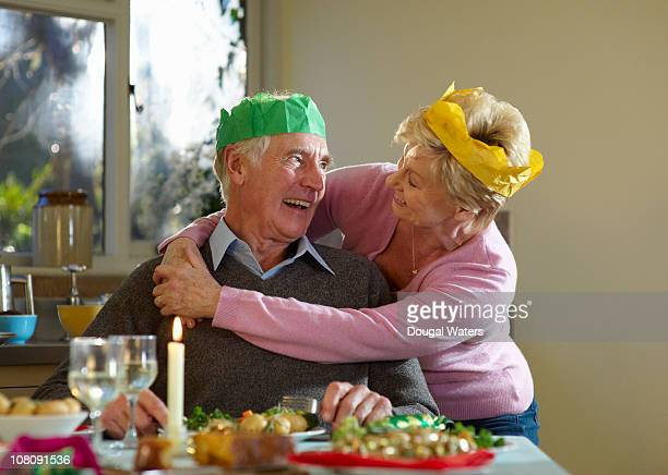 Senior couple embracing at dinner table.