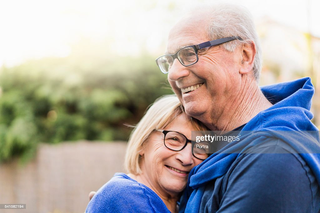 Senior couple embracing each other in backyard : Stockfoto
