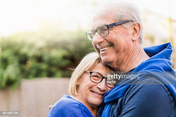 senior couple embracing each other in backyard - 60 64 years stock pictures, royalty-free photos & images