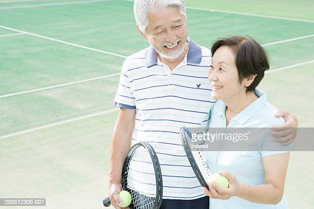 Senior couple embracing, holding tennis racquets and balls, smiling