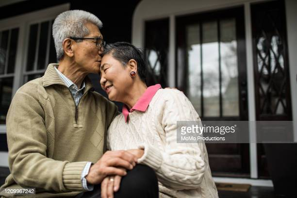 senior couple embracing in front of home - marryornot stock pictures, royalty-free photos & images
