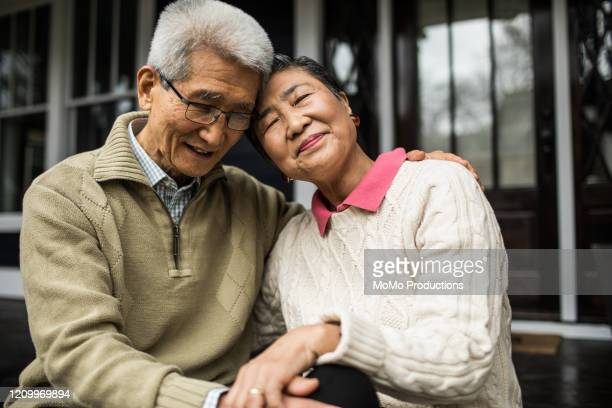 senior couple embracing in front of home - disruptagingcollection stock pictures, royalty-free photos & images