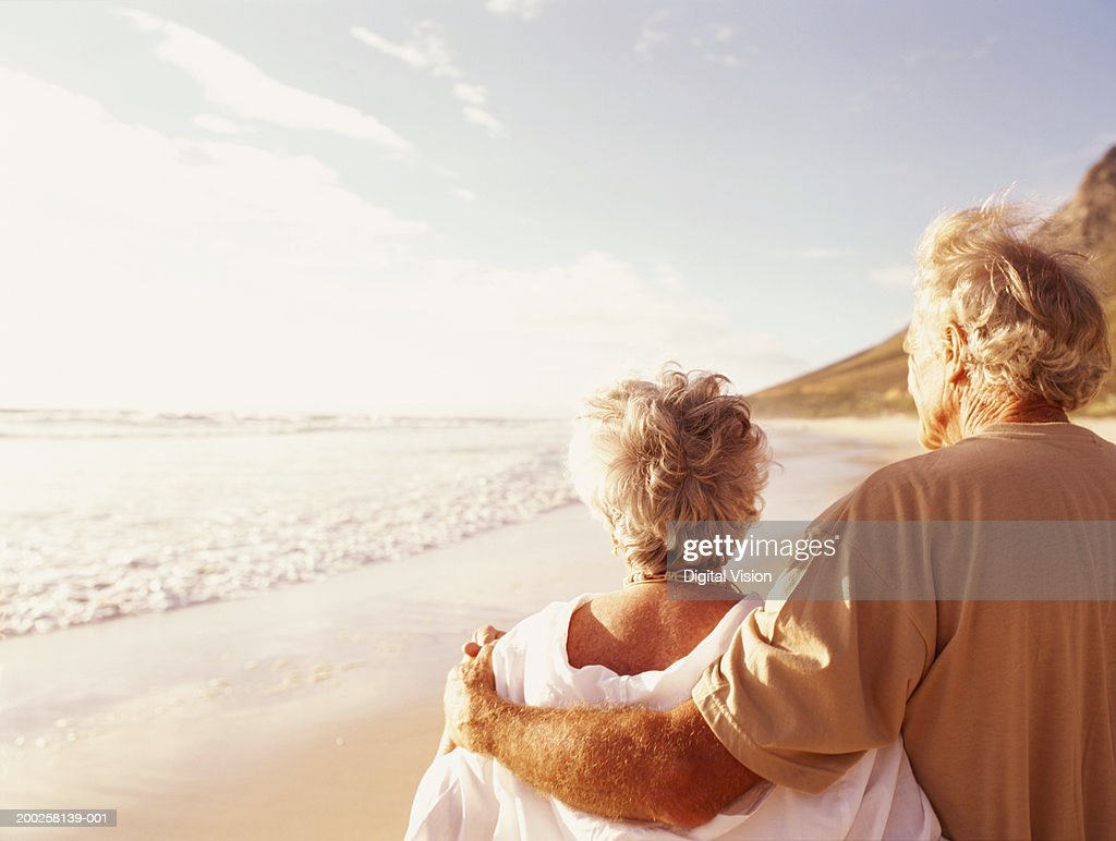 Senior couple embracing on beach, rear view : Stock Photo