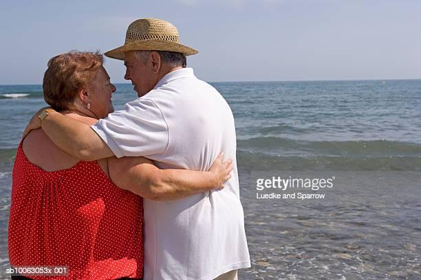 senior couple embracing on beach, rear view - dicke frauen am strand stock-fotos und bilder