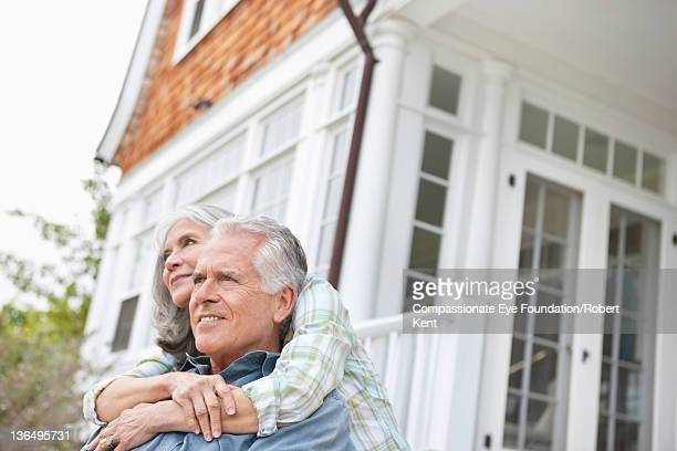 Senior couple embracing outdoors, smiling