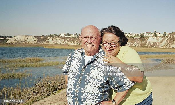 Senior couple embracing outdoors, smiling, portrait