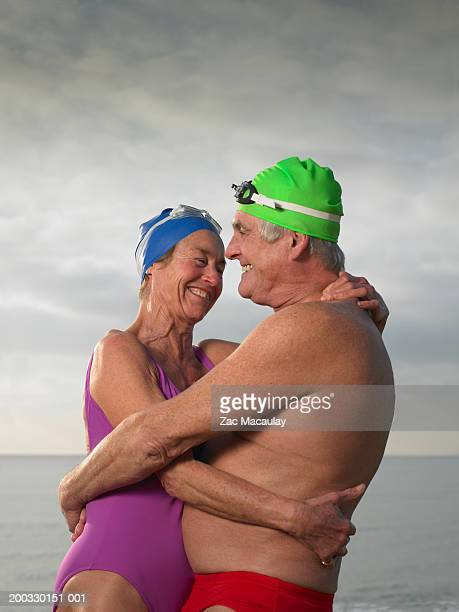 senior couple embracing wearing swimming caps and goggles - dicke frauen am strand stock-fotos und bilder