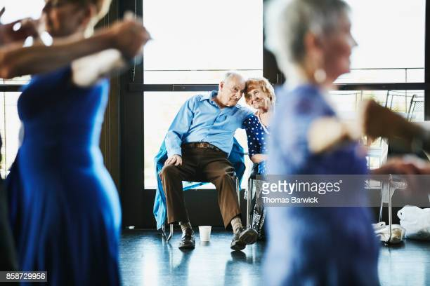 Senior couple embracing while resting during dance in community center