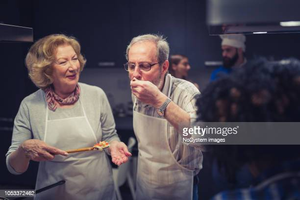 senior couple enjoy cooking class - attending stock pictures, royalty-free photos & images