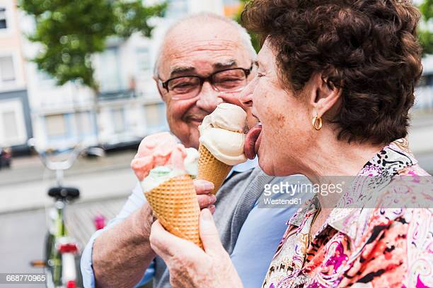 senior couple enjoy eating ice cream together - essen mund benutzen stock-fotos und bilder