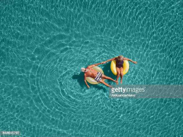senior couple enjoy sea water - summer stock pictures, royalty-free photos & images