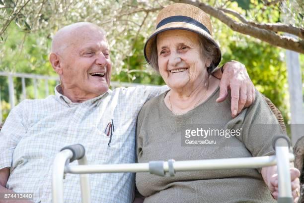 Älteres Paar genießen Sie den Sommer unter dem Baum Schatten sitzen