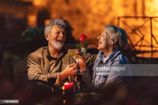 pareja mayor disfrutando de una copa de vino - prometido relación humana fotografías e imágenes de stock