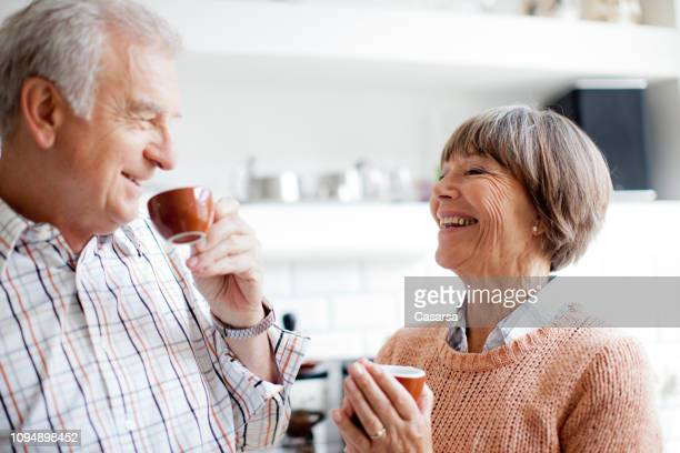senior couple enjoying an espresso in the kitchen - espresso stock photos and pictures