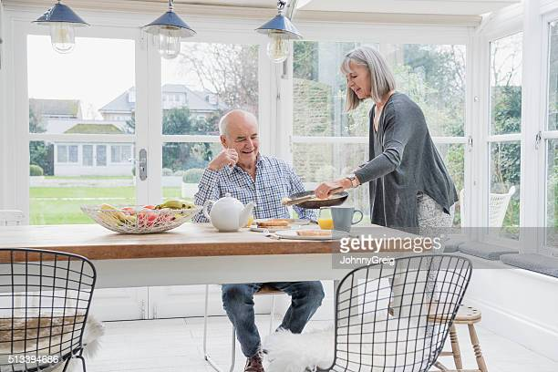 Senior couple enjoying breakfast at the dinner table