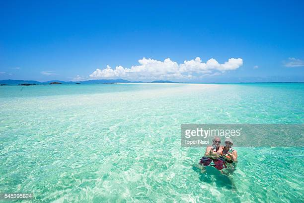 Senior couple enjoying clear tropical water and coral cay beach, Okinawa
