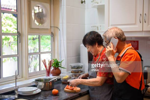 senior couple enjoying cooking in the kitchen - kitchenware shop stock pictures, royalty-free photos & images