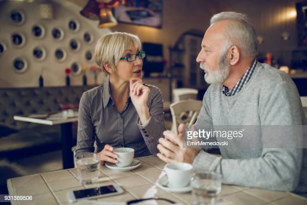 Senior couple enjoying cup of coffee in cafe