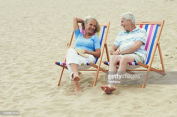 senior couple enjoying day out at the beach - chair stock pictures, royalty-free photos & images
