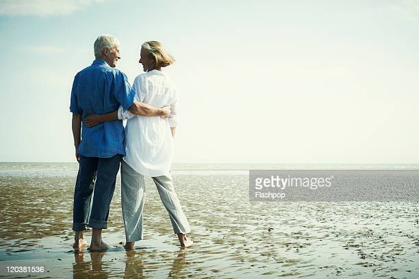 senior couple enjoying day out at the beach - senior couple stock pictures, royalty-free photos & images