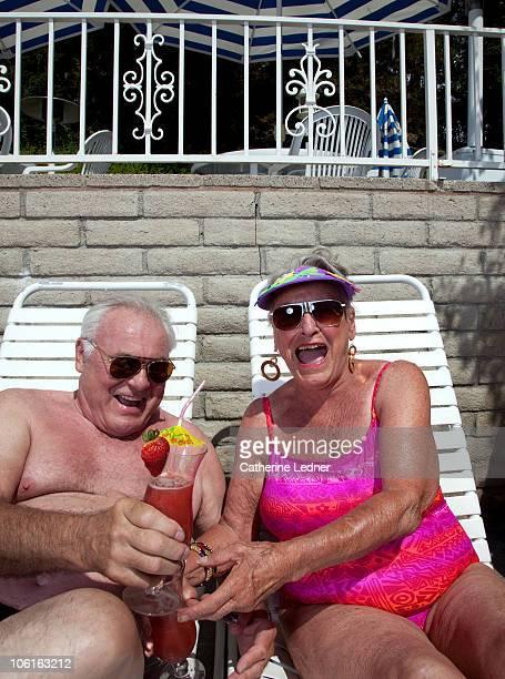 senior couple enjoying drinks while sunbathing. - sun lounger stock pictures, royalty-free photos & images
