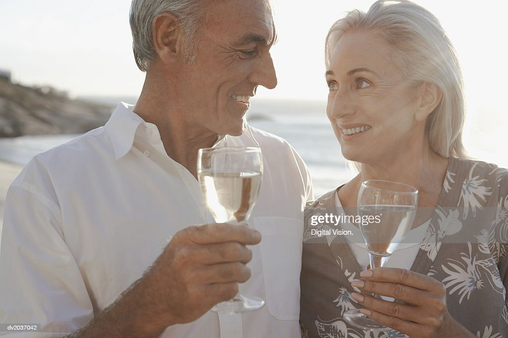 Senior Couple Enjoying Glasses of White Wine and Gazing at Each Other : Stock Photo