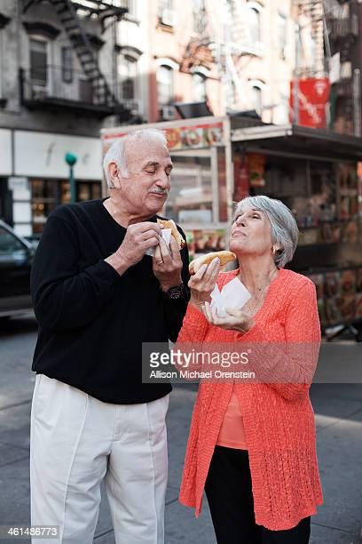 Senior couple enjoying hot dogs on city street