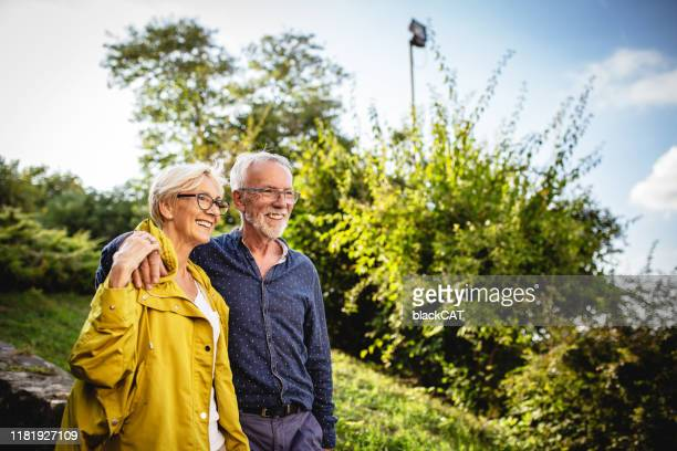 senior couple enjoying in park - retirement stock pictures, royalty-free photos & images
