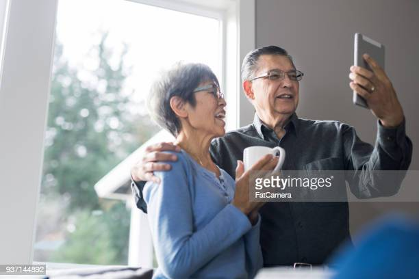 senior couple enjoying morning coffee together - pacific islander stock pictures, royalty-free photos & images