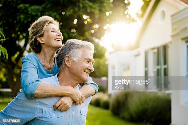 senior couple enjoying outside house on sunny day - 65 69 ans photos et images de collection