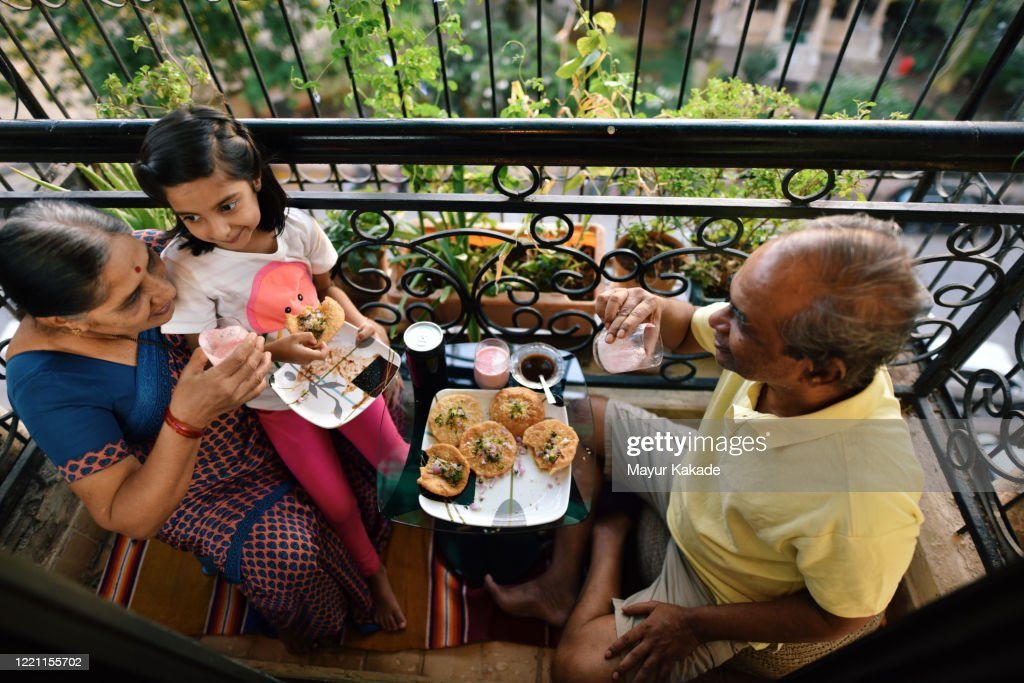 Senior couple enjoying snacks in the balcony with granddaughter : Stock Photo