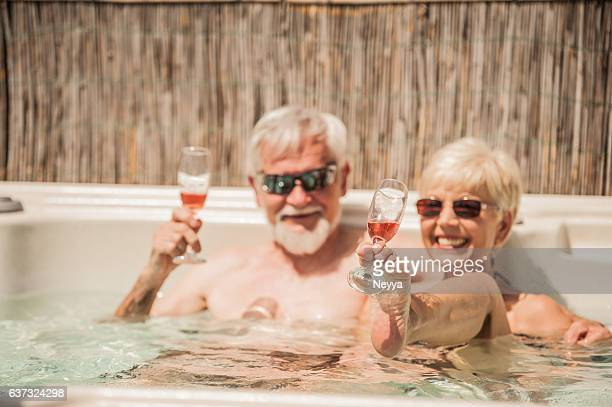 Senior Couple Enjoying Summer in Whirlpool with Sparkling Wine