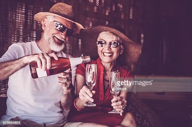 Altes Paar genießen Sommerurlaub mit Champagner
