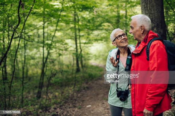 senior couple enjoying the beauties of the forest - binoculars stock pictures, royalty-free photos & images