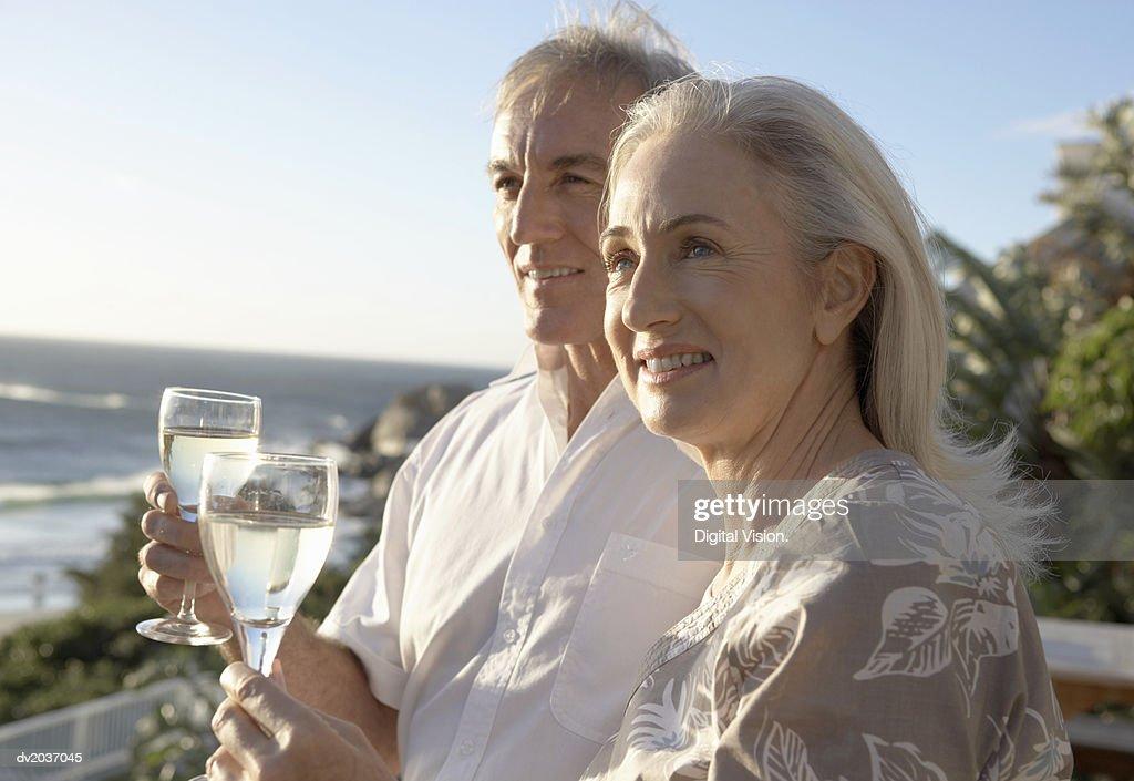 Senior Couple Enjoying Wine by the Sea : Stock Photo