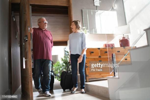couples aînés entrant la maison - renvoyer la balle photos et images de collection