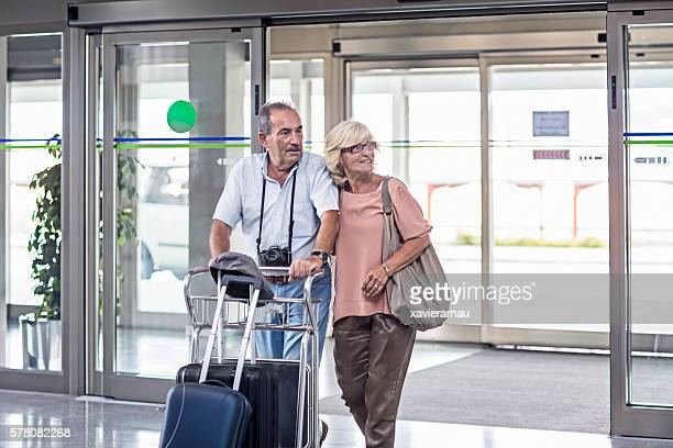 Senior couple entering with suitcase to the airport