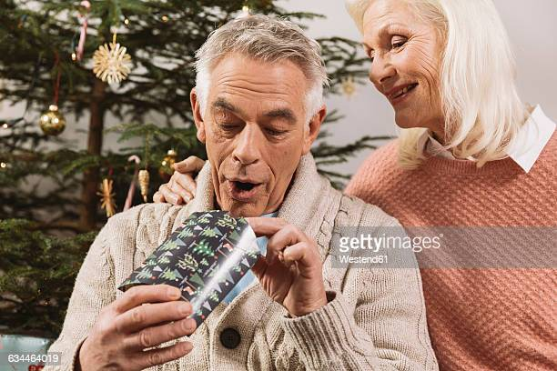 senior couple exchanging christmas gifts in front of tree - gift lounge stock-fotos und bilder