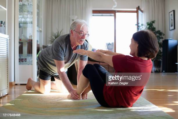 senior couple exercising at home - illness prevention stock pictures, royalty-free photos & images