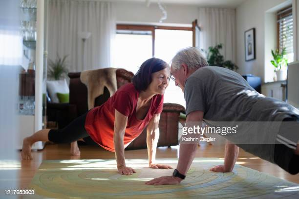 senior couple exercising at home - prevention stock-fotos und bilder