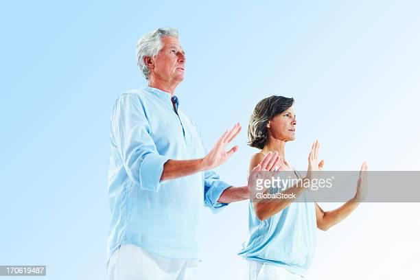 couple de personnes âgées exerçant sur fond bleu