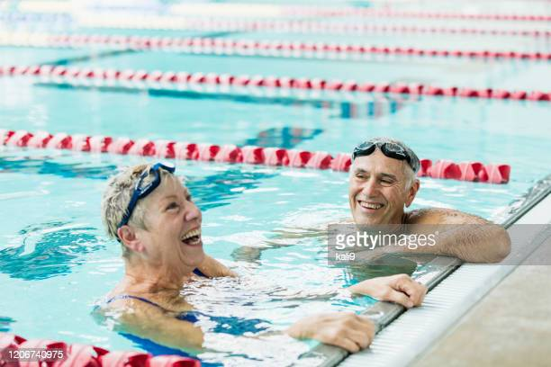 senior couple exercising together, swimming laps - length stock pictures, royalty-free photos & images