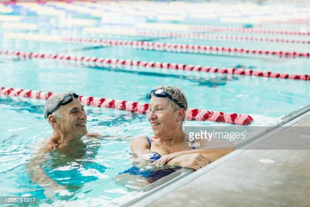 senior couple exercising together, swimming laps - leisure facilities stock pictures, royalty-free photos & images